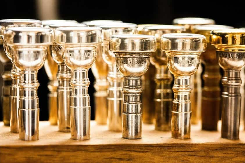 Different models of golden 7C trumpet mouthpieces.