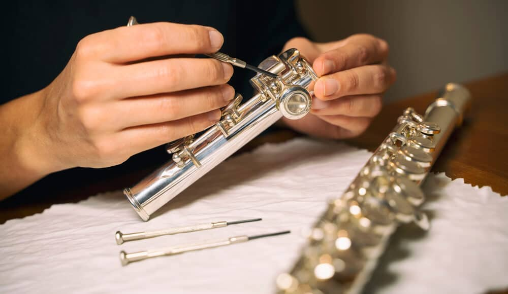 Musical instrument technician is assembling flute parts.