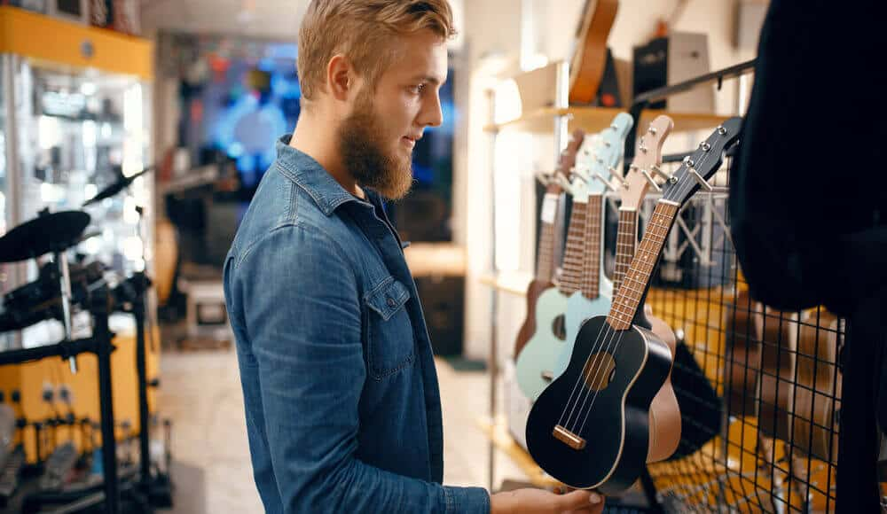 Student picking ukulele models in the musical instrument shop.