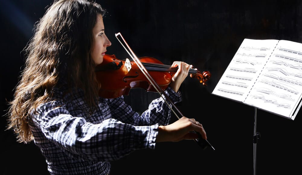 Violin student is practising different bowing techniques in studio.