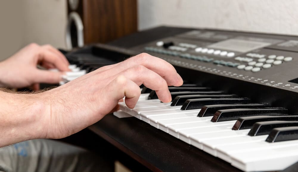 Beginner is learning how to play keyboard piano.