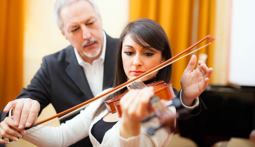 Violin teacher teaching student how to play violin.
