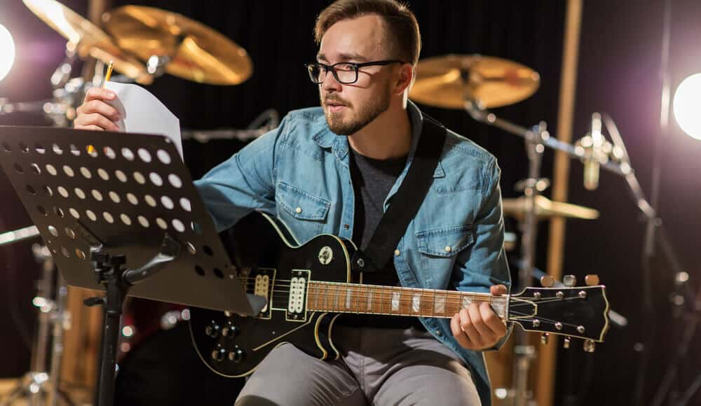 Guitarist use music stand during live gig performance.
