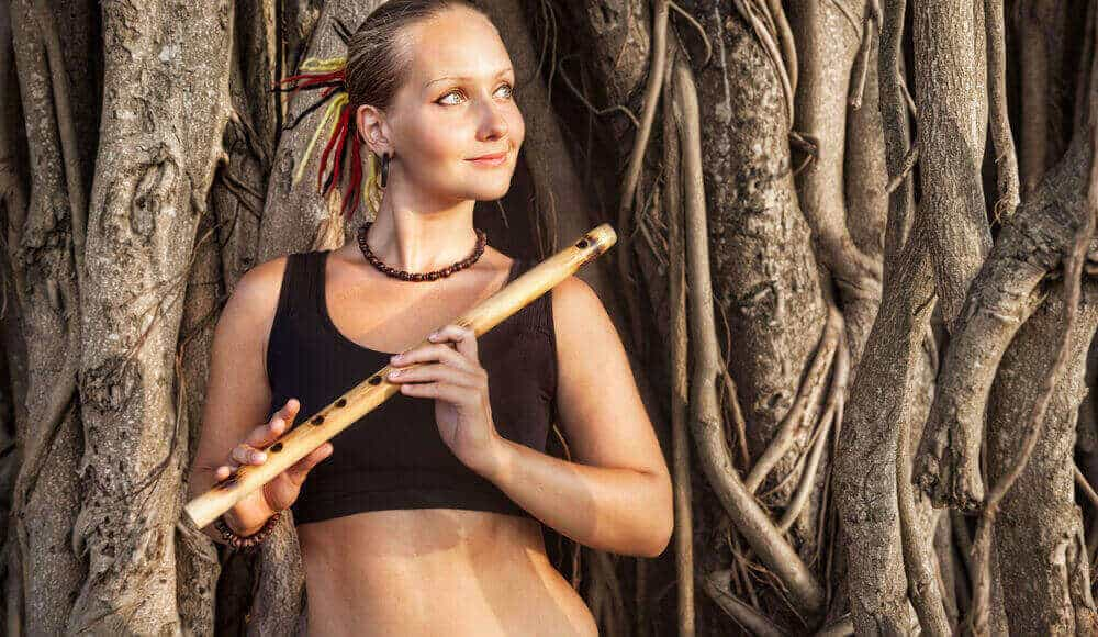 Female plays wooden flute.