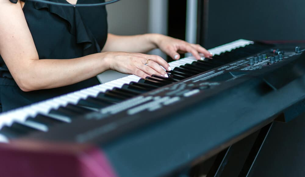 Pianist is playing the digital keyboard in sitting position.