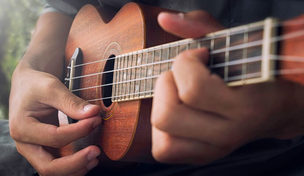 Musician playing plunking the Ukulele strings.
