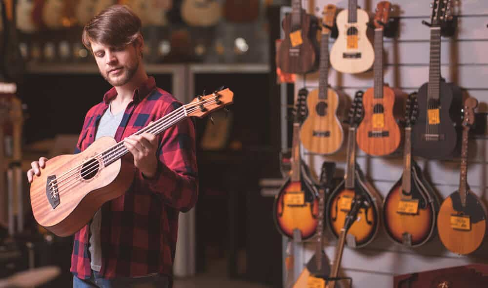Man is choosing suitable ukulele in the musical instrument shop.